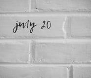 20 juillet ÉCRIT SUR le MUR DE BRIQUES SIMPLE BLANC Photo stock