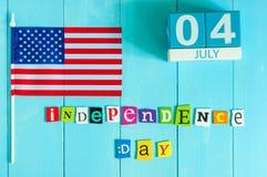 4 juillet calendrier en bois de couleur avec le drapeau de bannière étoilée sur le fond bleu Arbre dans le domaine L'espace vide  Image libre de droits