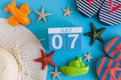 7 juillet Image de calendrier du 7 juillet avec les accessoires de plage d'été et l'équipement de voyageur sur le fond Jour d'été Image stock