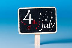 4 juillet Image de calendrier du 4 juillet sur peu d'étiquette au fond bleu Arbre dans le domaine L'espace vide pour le texte Fon Image libre de droits