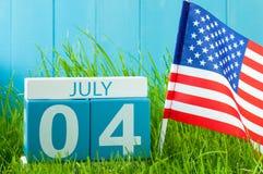 4 juillet Image de calendrier en bois de couleur du 4 juillet sur le fond bleu avec le drapeau des Etats-Unis Arbre dans le domai Photos stock