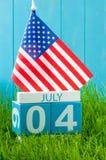 4 juillet Image de calendrier en bois de couleur du 4 juillet sur le fond bleu avec le drapeau des Etats-Unis Arbre dans le domai Images libres de droits