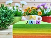juillet Lettres colorées de cube sur le bloc collant de note photos libres de droits