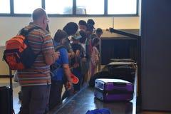2016 juillet Verona Italy - les touristes attendent le bagage sur le convoyeur pour des valises Images stock
