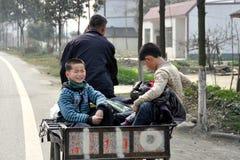 Juin Le Town, Chine : Deux petits garçons dans le chariot Photos stock