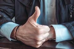 Juiste mannelijke hand met een rozentuin op de pols en een omhoog opgeheven duim Close-up stock afbeeldingen