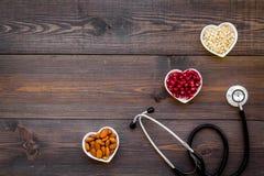 Juiste voeding voor pathients met hartkwaal De cholesterol vermindert dieet Havermeel, granaatappel, amandel in gevormd hart stock afbeelding