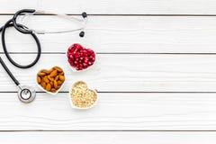 Juiste voeding voor pathients met hartkwaal De cholesterol vermindert dieet Havermeel, granaatappel, amandel in gevormd hart stock foto