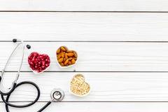 Juiste voeding voor pathients met hartkwaal De cholesterol vermindert dieet Havermeel, granaatappel, amandel in gevormd hart stock foto's
