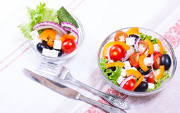 Juisy vegetables in salade. Greek salad in a transparent bowl and ingredients Royalty Free Stock Image