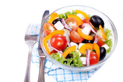 Juisy vegetables in salade. White background. Greek salad in a transparent bowl and ingredients. White background Stock Image