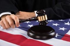 Juiz Hands With Gavel e bandeira americana Foto de Stock