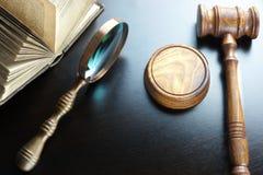 Juizes martelo, lente de aumento e livro velho na tabela preta Fotografia de Stock