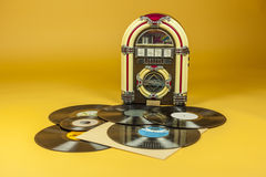 Jukebox and some old vinil records. Isolated in yellow background Royalty Free Stock Image