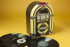 Jukebox and some old vinil records. In yellow background Royalty Free Stock Images