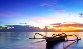 Jukung Traditional Bali Fishing Boat. On sunrise near sanur beach facing the ocean.  The traditional style canoe is fitted with two bamboo act as stabilisers