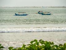 Jukungs ankrade av kust på Kuta Bali royaltyfri foto