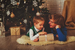 Jul önskar fadern och sonen som tar gåvor i dekorerad vardagsrum Royaltyfria Foton