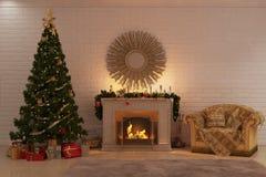 Jul avfyrar nära en julgran med gåvor och en hemtrevlig fåtölj Arkivfoton