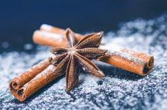 Jul Backround Kanel med stjärnan anize på ett mjöl och en mörk tabell Mjöl och kryddor för baka för jul Arkivfoton