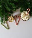 Jul bakgrund, hälsningkort med en kopp kaffe eller choklad med marshmallower, klubbor, en röd platta och trädfilialer stock illustrationer