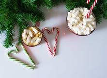 Jul bakgrund, hälsningkort med en kopp kaffe eller choklad med marshmallower, klubbor, en röd platta och trädfilialer royaltyfri illustrationer