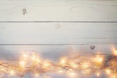 Jul bakgrund och ljusgirland på wood bakgrund med Royaltyfri Fotografi