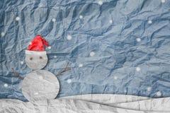 Jul bakgrund, snögubbe som bär den röda jultomtenhatten i vinter med snö, papperssnitt som göras av skrynkligt papper arkivbild