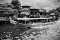 Thai long tail boat with garlands in Banhkok canal Klong, famo. JUL 10, 2018 Bangkok, Thailand - Thai long tail boat with garlands in Banhkok`s canal royalty free stock images