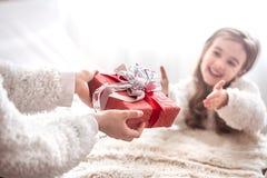 Jul begreppet, mamma ger en gåva till lite gullig dotter, a royaltyfria foton
