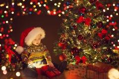 Jul behandla som ett barn den öppna närvarande gåvaasken under Xmas-trädet, lycklig unge arkivbild