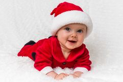Jul behandla som ett barn i den Santa Claus dräkten som ligger på den vita filten arkivbilder