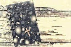 Jul Bibel och kors på en gammal vit bakgrund fallande snowflakes Fotografering för Bildbyråer