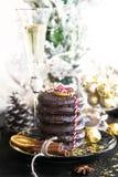Jul, bröd och sötsaker för xmas ljust rödbrun, kakor på den svarta plattan, guld- bollar och konfettier med kanel, anis royaltyfria foton