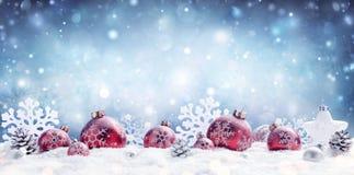 Jul - dekorerade röda struntsaker och snöflingor royaltyfria foton