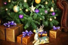 Jul dekorerade trädet med gåvor hjortar och soffa Royaltyfria Foton