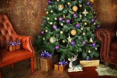 Jul dekorerade trädet med gåvor hjortar och soffa Arkivfoton