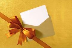 Jul eller födelsedagkort, diagonal guld- gåvabandpilbåge, tomt kort och kuvert, kopieringsutrymme Arkivbilder
