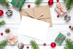 Jul förbigår hälsningkortet i ram av granfilialer, bollar, röda bär, gåvaaskar och kottar royaltyfria foton