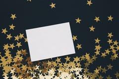 Jul förlöjligar upp greetengkort på svart bakgrund med guld- stjärnakonfettier Inbjudan papper Ställe för den lekmanna- textlägen royaltyfri bild