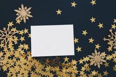 Jul förlöjligar upp hälsningkort på svart bakgrund med blänker konfettier för stjärnor för snöflingaprydnader guld- Inbjudan papp royaltyfri fotografi