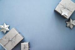 Jul försilvrar handgjorda gåvaaskar på bästa sikt för blå bakgrund Hälsningkort för glad jul, ram Tema för vinterxmas-ferie royaltyfri fotografi