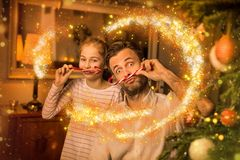 Jul - fader och dotter som spelar med godisrottingar Arkivfoton