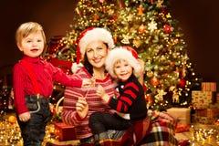 Jul familjen, moder med barn beklär av Xmas-trädljus, lycklig mamma och behandla som ett barn royaltyfria bilder