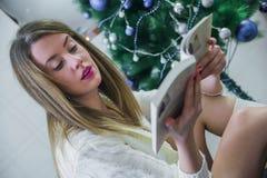 Jul, ferier och folkbegrepp - lycklig läsebok för ung kvinna hemma Festlig brunettläsning på soffan hemma Arkivbild
