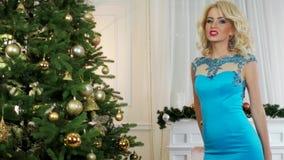 Jul flickan ger nytt års gåva, nära julgranen och spisen på som de tända stearinljusen, kvinna stock video