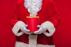 Jul Foto av Santa Claus den behandskade handen med en röd hink med popcorn, på en röd bakgrund Royaltyfri Foto