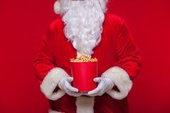 Jul Foto av Santa Claus den behandskade handen med en röd hink med popcorn, på en röd bakgrund Arkivfoto