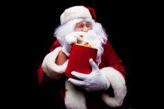 Jul Foto av Santa Claus den behandskade handen med en röd hink med popcorn, på en svart bakgrund Arkivbilder