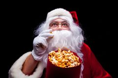 Jul Foto av Santa Claus den behandskade handen med en röd hink med popcorn, på en svart bakgrund Arkivbild
